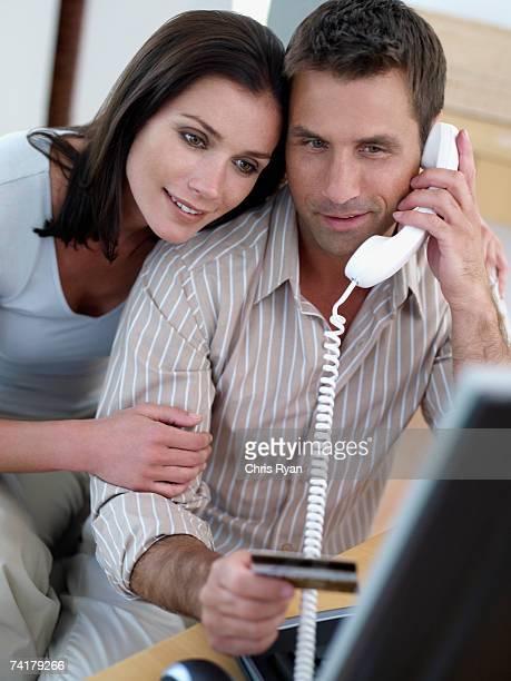 Mann mit Kreditkarte und computer mit Frau