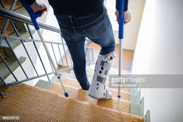 A man with crutches and an orthosis on his leg walks down a staircase on January 15 2018 in Berlin Germany