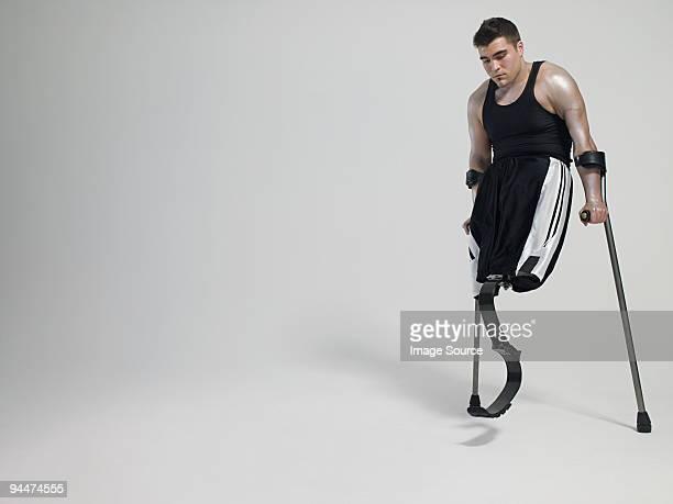 Homme avec des béquilles et jambes artificielles.
