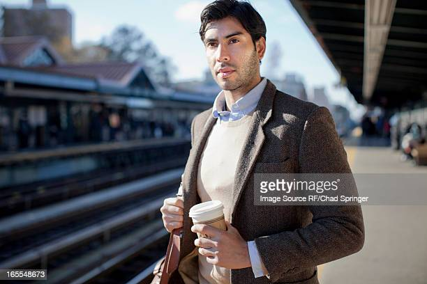 Man with cup of coffee at train station