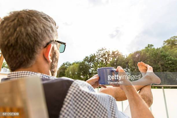 Man with cup of coffee relaxing on his balcony