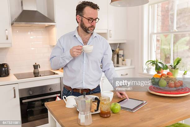 Man with cup of coffee standing in the kitchen using digital tablet