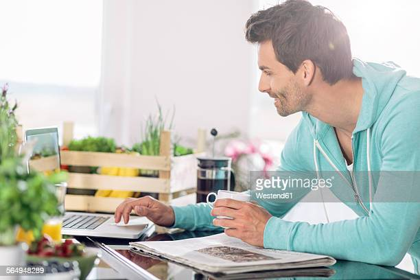 Man with cup of coffee using laptop in the kitchen