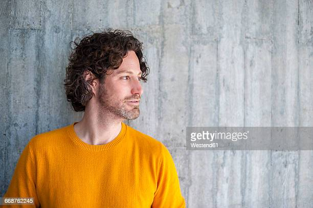 man with curly brown hair leaning against concrete wall - pull photos et images de collection