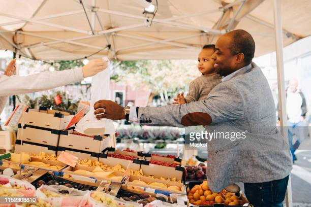 man with daughter buying fruit and vegetables from female seller in market stall - ファーマーズマーケット ストックフォトと画像