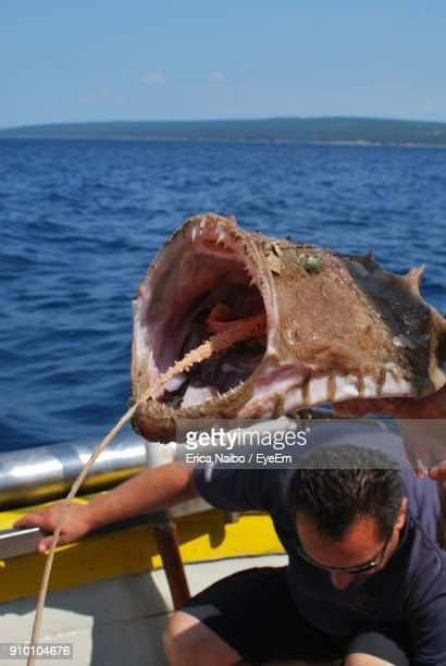 man with dead fish on boat in sea - dead man stock pictures, royalty-free photos & images