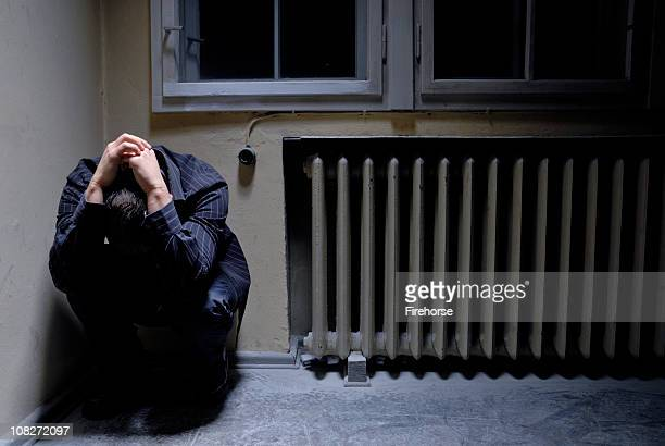 Man with deep depression in the corner of a room
