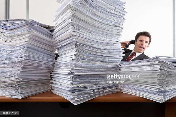 man with desk invaded by documents