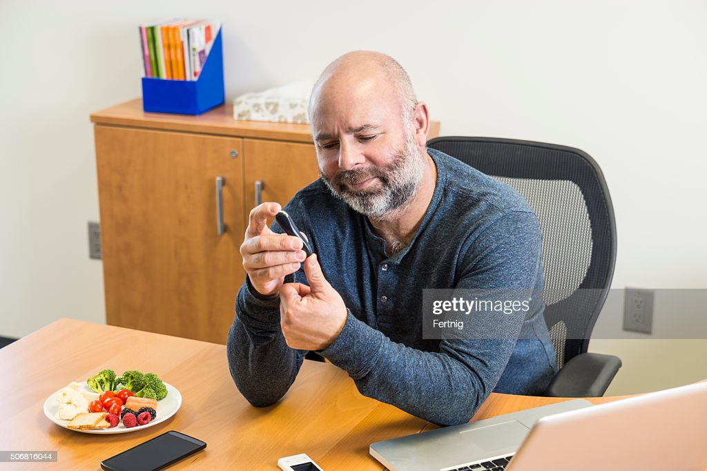 Man with diabetes taking a blood sample at work : Stock Photo