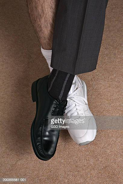 Man with differently dressed feet and legs crossed at ankles