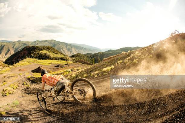 Man with differing abilities riding fast down a volcanic rock mountain during sunset.