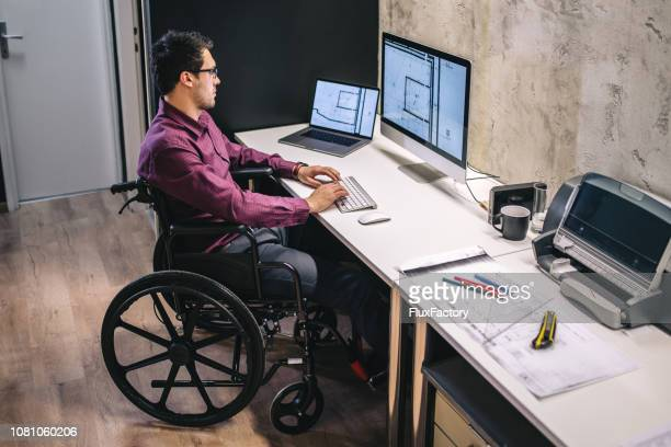 man with differing abilities working in the office - acessibilidade imagens e fotografias de stock