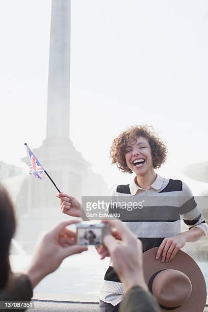 Homme avec caméra numérique prenant photo de femme heureuse avec petit déjeuner