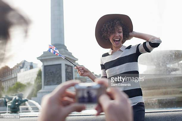 man with digital camera taking photograph of happy woman with british flag in front of fountain - trafalgar square stock pictures, royalty-free photos & images