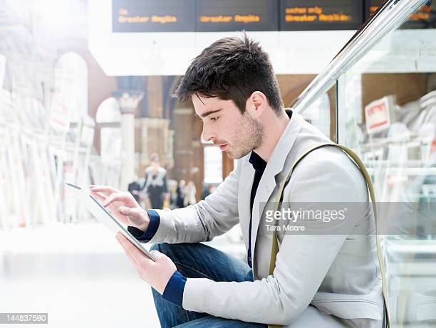 man with digital tablet at train station - newtechnology stock pictures, royalty-free photos & images