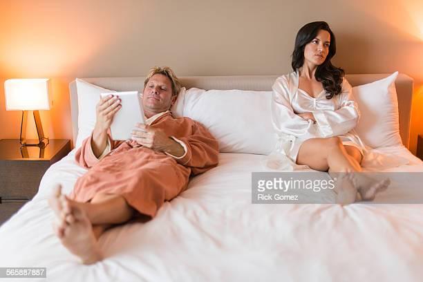 Man with digital tablet ignoring girlfriend in bed