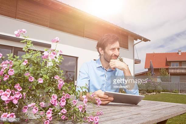 Man with digital tablet in garden