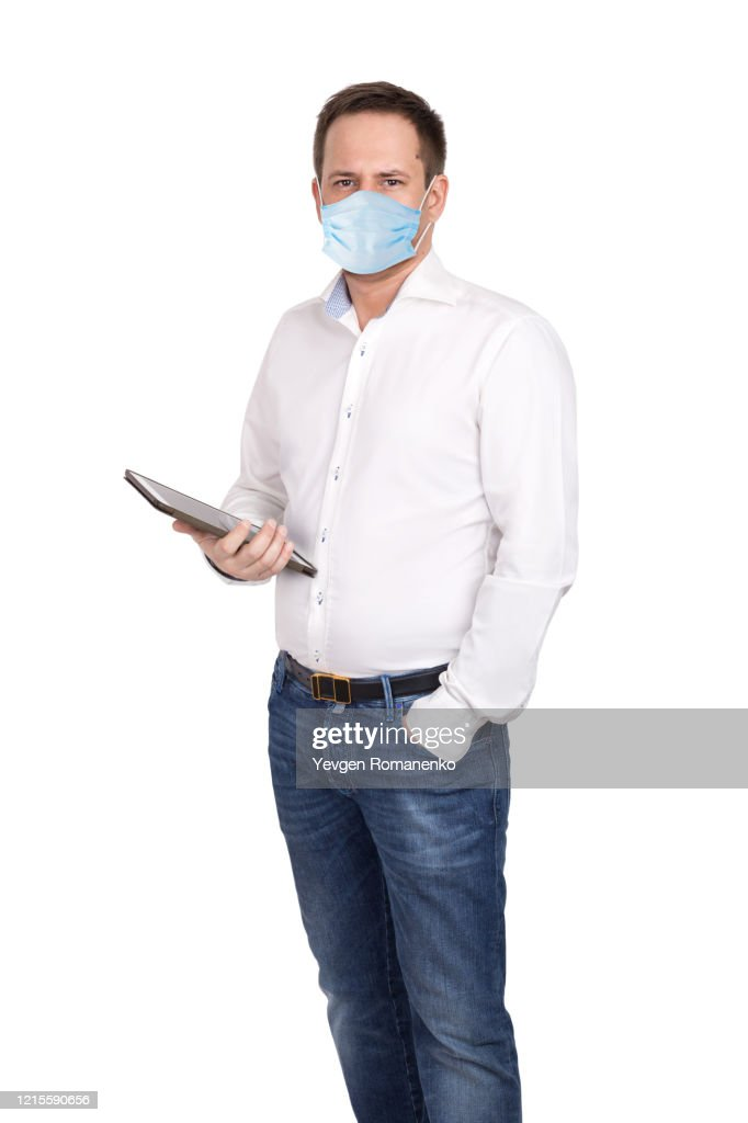 Man with digital tablet in white shirt and jeans wears surgical mask to protect from virus. Isolated on white background : ストックフォト