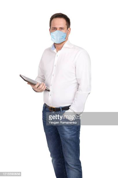 man with digital tablet in white shirt and jeans wears surgical mask to protect from virus. isolated on white background - メンズウェア ストックフォトと画像