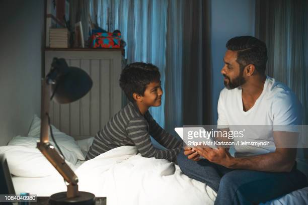 man with digital tablet looking at son in bedroom - bedtime stock pictures, royalty-free photos & images