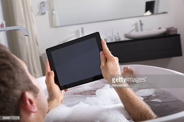 Man with digital tablet sitting in bathtub