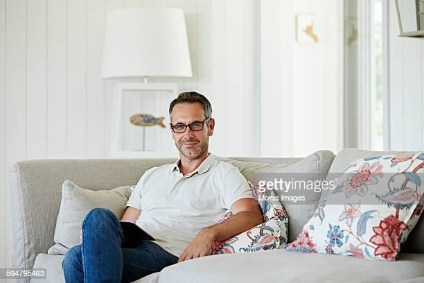 man with digital tablet sitting on sofa - ポロシャツ ストックフォトと画像