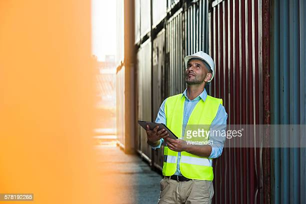 Man with digital tablet wearing reflective vest at container port