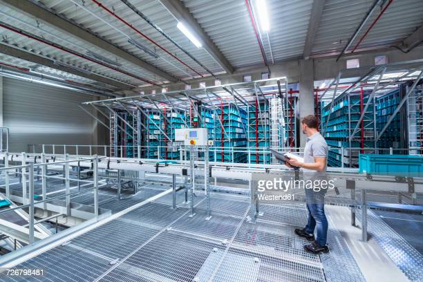 Man with documents in automatized high rack warehouse