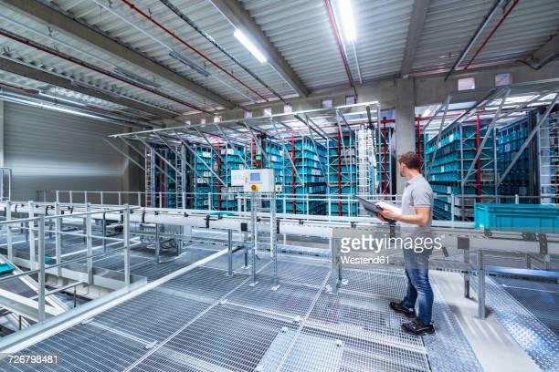 man with documents in automatized high rack warehouse - halle gebäude stock-fotos und bilder
