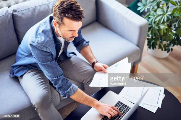 man with documents sitting on sofa using laptop - human body part stock pictures, royalty-free photos & images