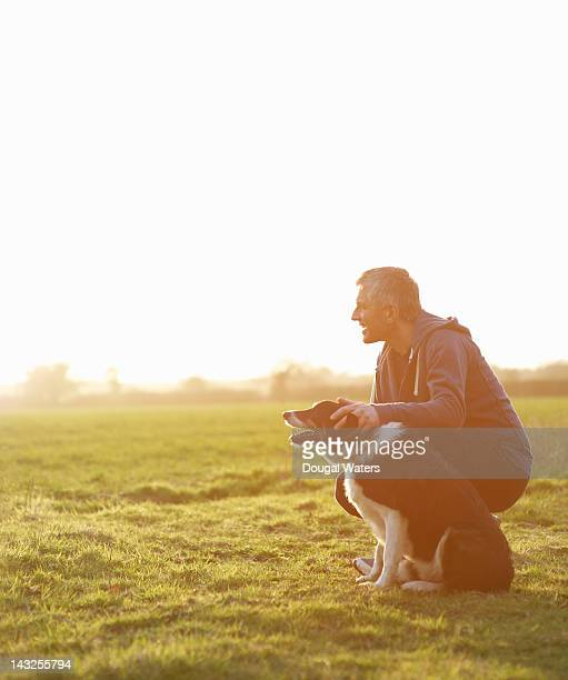 Man with dog at sunset in countryside.