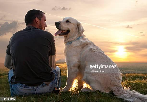 Mann mit Hund bei Sonnenuntergang