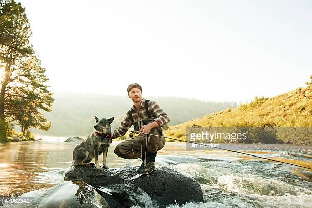 Man with dog fishing in river