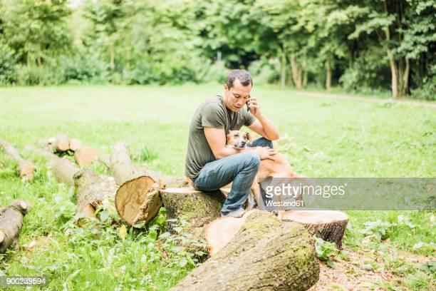 man with dog in a park talking on cell phone - alleen één mid volwassen man stockfoto's en -beelden