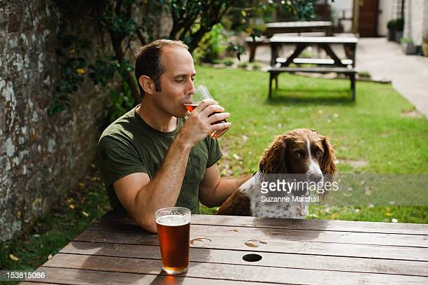 man  with dog in pub garden - pub stock pictures, royalty-free photos & images