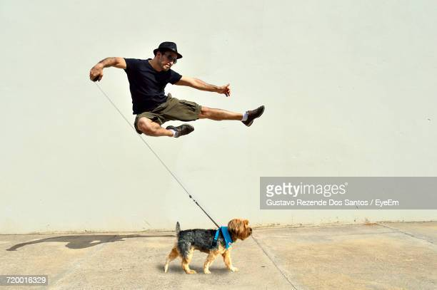Man With Dog Jumping By Wall