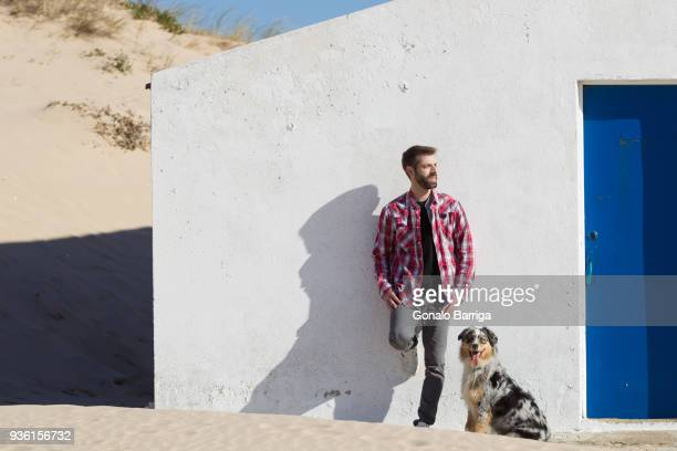 man with dog leaning against wall at beach - whitewashed stock pictures, royalty-free photos & images