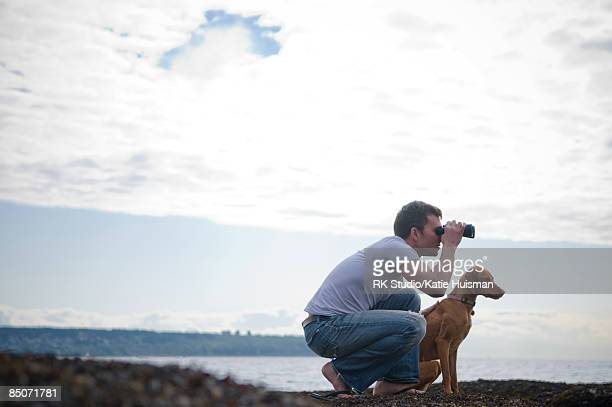 Man with dog looking through binoculars to ocean.