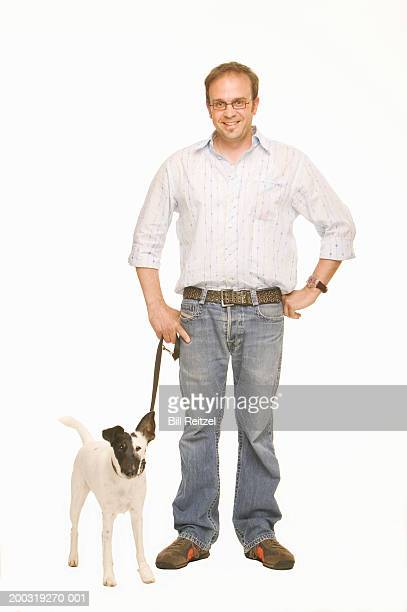 Man with dog on leash, smiling, portrait