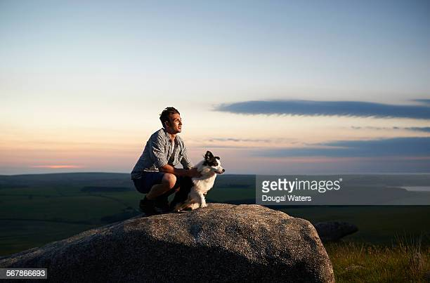 Man with dog on rocky hilltop.