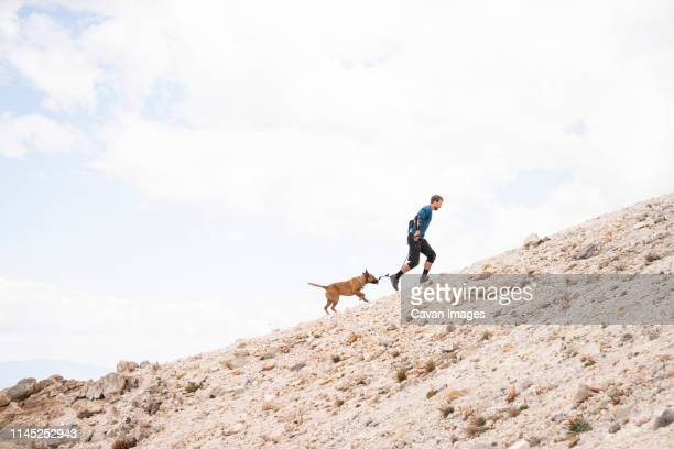 man with dog running on mountain against cloudy sky - alleen één mid volwassen man stockfoto's en -beelden