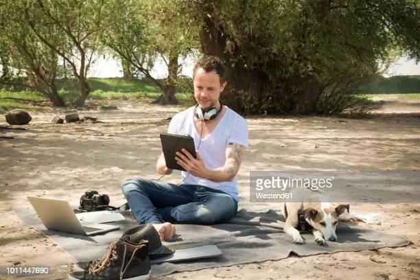 man with dog sitting on blanket at a beach using tablet - freischaffender stock-fotos und bilder