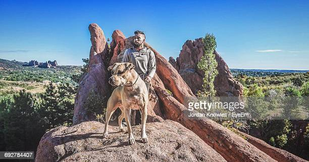 man with dog standing at red rock canyon national conservation area against sky - nevada stock-fotos und bilder