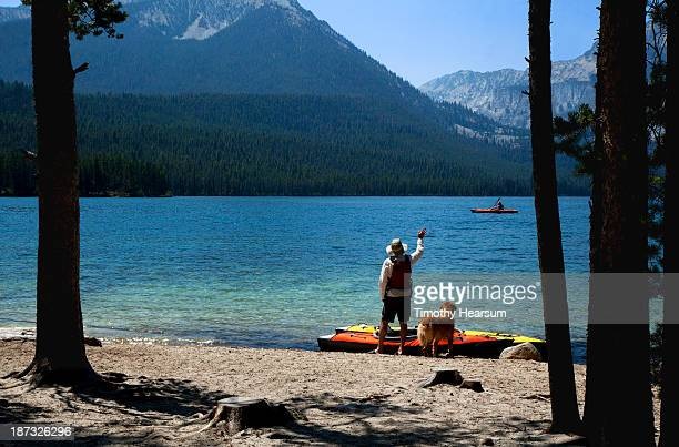 man with dog waves to kayaker on pristine lake - timothy hearsum stock pictures, royalty-free photos & images