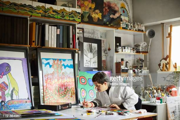 man with down syndrome painting in studio - disabilitycollection stock-fotos und bilder