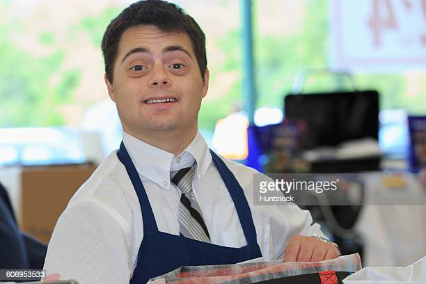man with down syndrome working at a grocery store - discapacidad intelectual fotografías e imágenes de stock