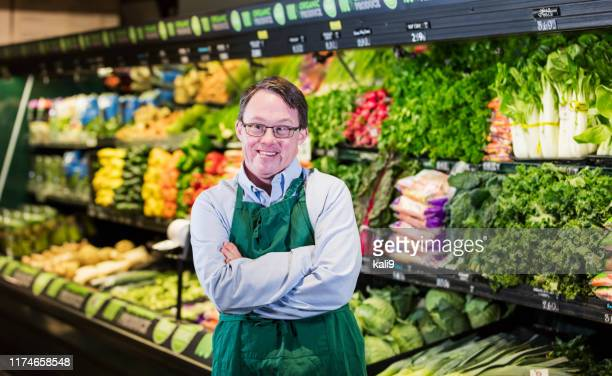 man with down syndrome working in supermarket - persons with disabilities stock pictures, royalty-free photos & images