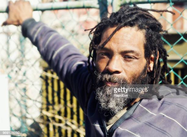 man with dreadlocks leans against a gate - dreadlocks stock pictures, royalty-free photos & images