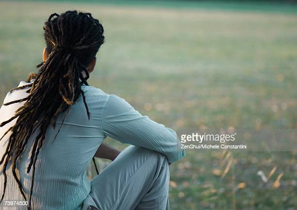 Man with dreadlocks sitting outside, rear view