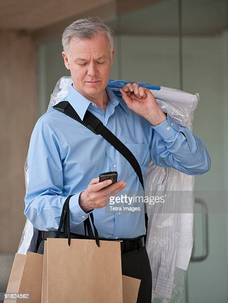A man with dry cleaning and shopping bags